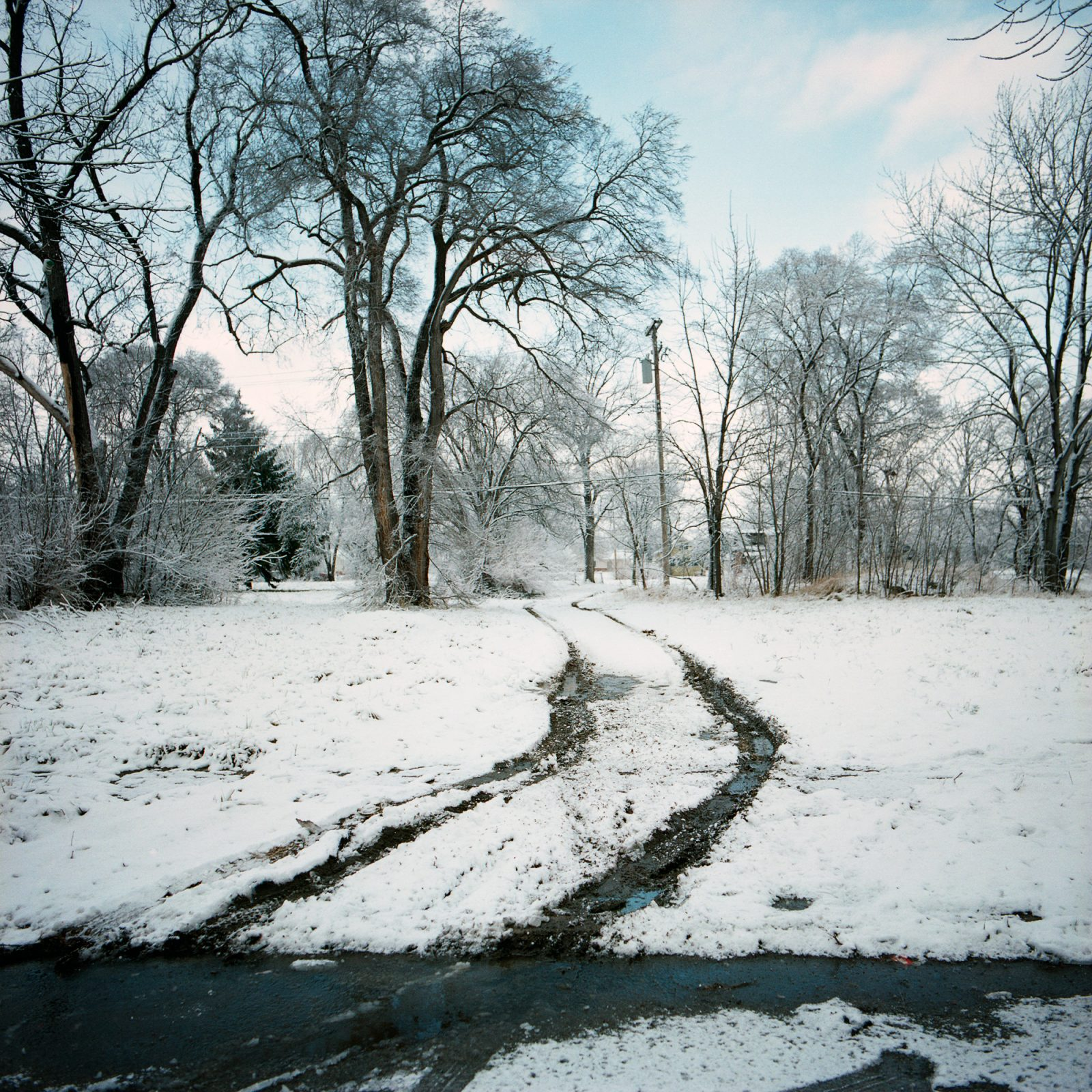 Tire tracks in snow, in abandoned neighborhood in Detroit.